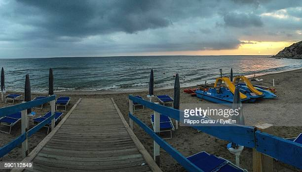 Wooden Pier By Sea Against Cloudy Sky During Sunset