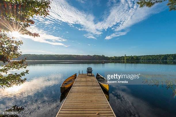 Wooden pier reaches into tranquil lake, sunrise