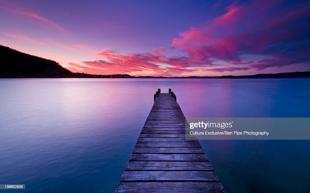 Wooden pier stretching into still lake : Stock Photo