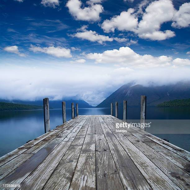Wooden planked pier along lakeside welcoming to paradise