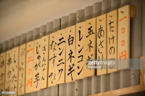 Wooden planks displaying menu items hang from a wall at a Kushikatsu Tanaka restaurant operated by Kushikatsu Tanaka Co stands in Tokyo Japan on...
