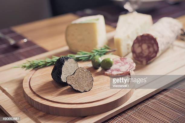 Wooden plate with truffles, cheese and salami