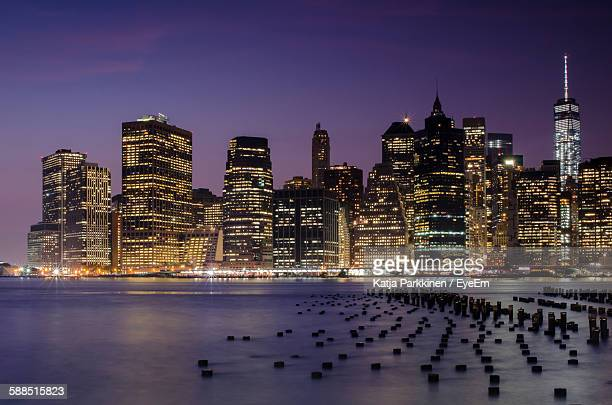 Wooden Posts In East River By Illuminated Cityscape At Dusk