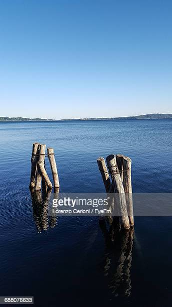 Wooden Posts In Lake Against Clear Blue Sky