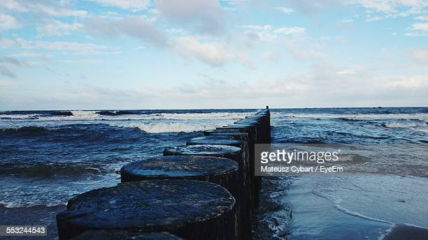 Wooden Posts In Sea Against Cloudy Sky