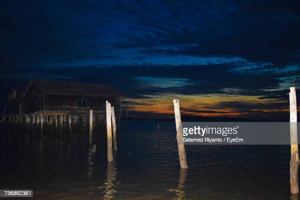 Wooden Posts In Sea Against Sky At Night