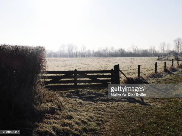 Wooden Posts On Grass Against Sky