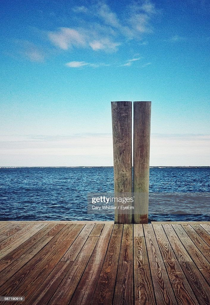 Wooden Posts On Pier Over Sea Against Sky