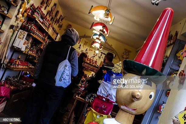 A wooden puppet depicting Italian character Pinocchio is installed outside a shop in central Rome on December 9 2014 AFP PHOTO / ANDREAS SOLARO