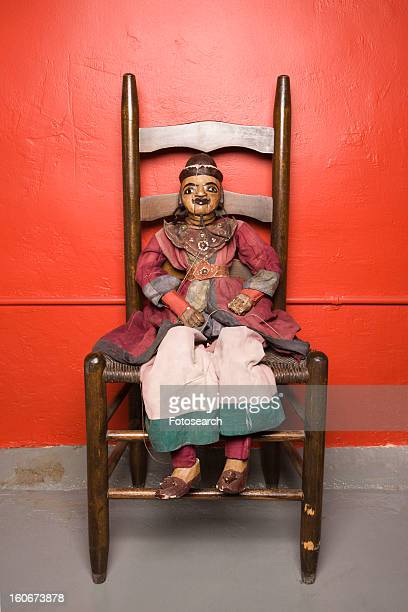 Wooden puppet sitting on chair