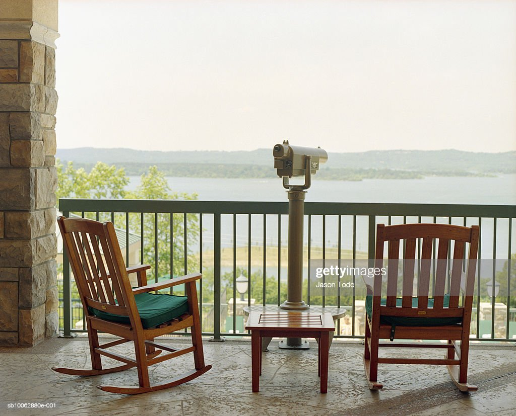 wooden rocking chairs and telescope on terrace rear view lake in background stock