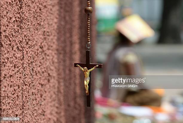 A wooden rosary with an image of the crucifixion of Jesus Christ is displayed at a roadside shop in New Delhi on April 3 on Good Friday Christians...