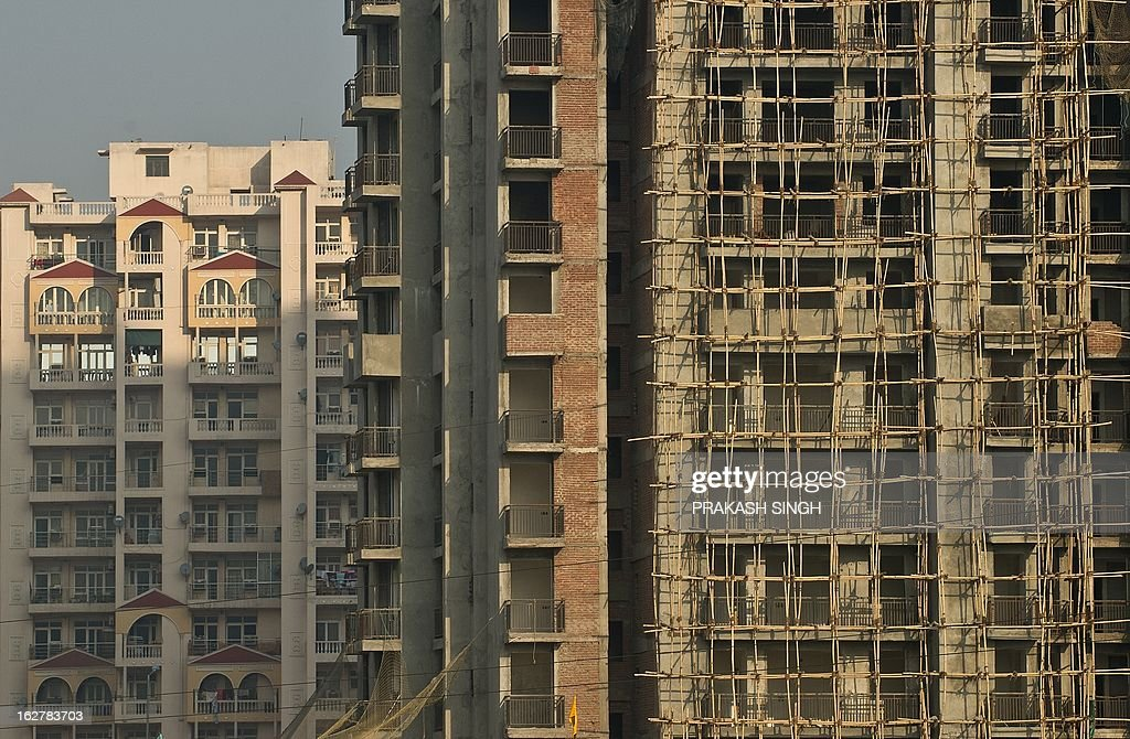 Wooden Scaffolding (R) is seen surrounding a high-rise residential complex undergoing construction in Ghaziabad, on the outskirts of New Delhi, on February 27, 2013. Indian Finance Minister P. Chidambaram will present the Union Budget 2013 in Parliament on February 28. AFP PHOTO/ Prakash SINGH