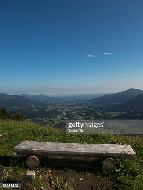 Wooden seat on mountain against blue sky