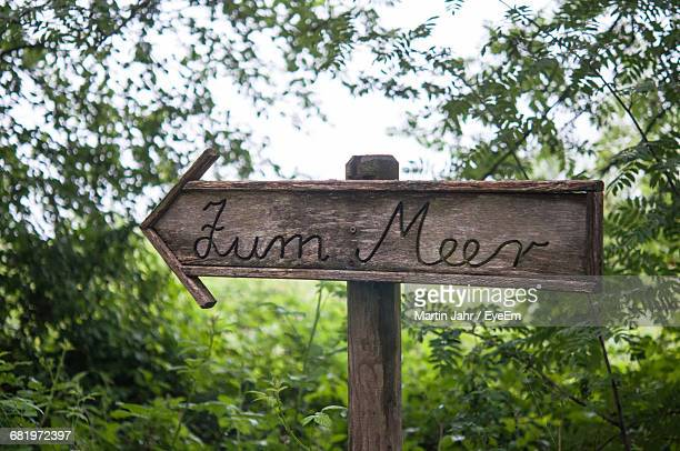 Wooden Sign Board Against Trees