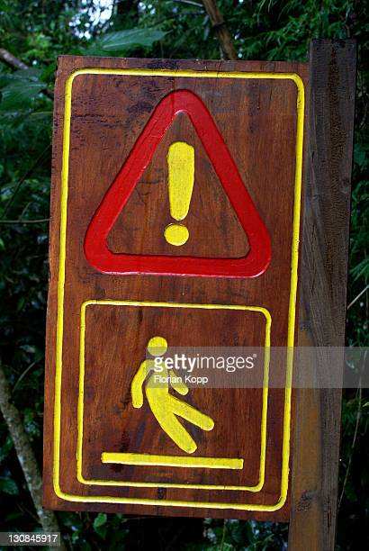 Wooden sign for take care, slippery