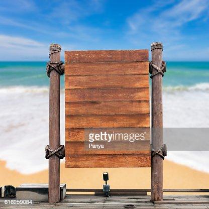 wooden signboard on blur beach background. : Stock Photo