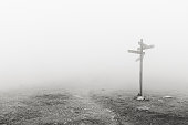wooden signpost in the fog. Black and white