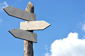 Wooden signpost with 3 arrows, blue sky in background.