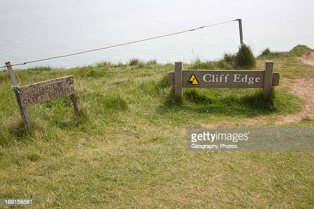 Wooden signs warning of the danger of cliff erosion at the top of the sheer cliffs at Beachy Head East Sussex England