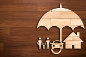 Wooden silhouette of family under umbrella - Concept of Insurance