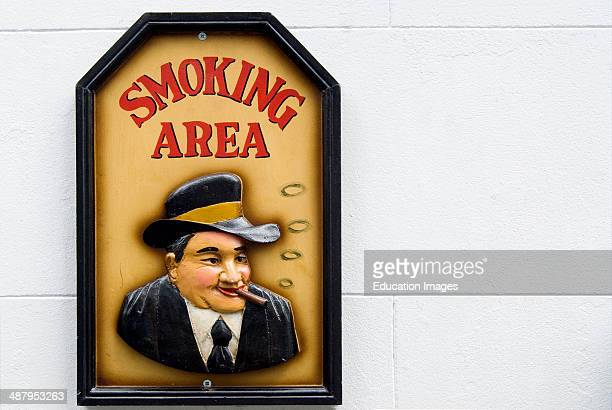 Wooden smoking area sign on a white wall outside of a English pub