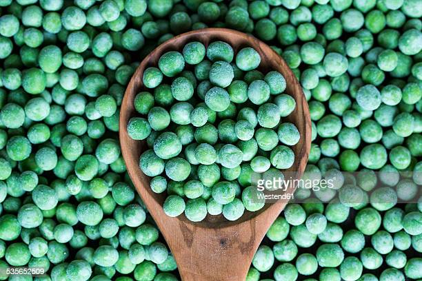 Wooden spoon and frozen peas