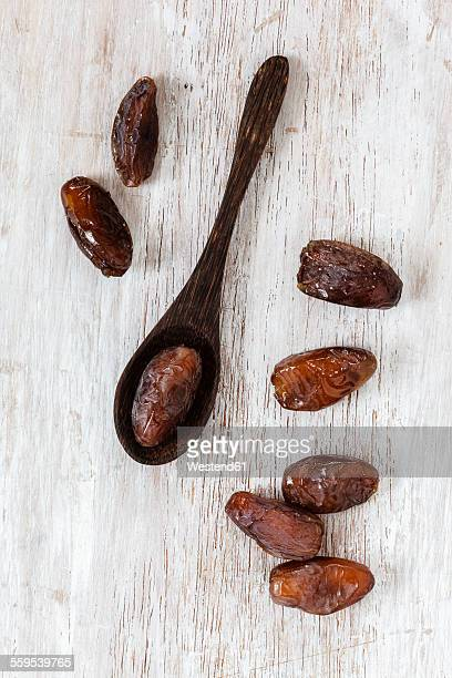 Wooden spoon and Medjooll dates on wood
