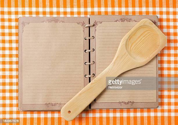 Cuillère en bois et vieux carnet sur orange tableclot
