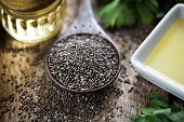 Wooden spoon with chia seeds (salvia hispanica) and oil