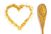 Wooden spoon with a long handle is filled with sesame seeds. Heart.  Isolated on white. The concept- kitchen, cooking, vegetarianism, healthy food.
