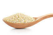 Wooden spoon with sesame seeds isolated on white background. Close-up.