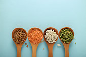 wooden spoons and various legumes on a uniform background