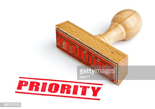 A wooden stamp about priority in a white background