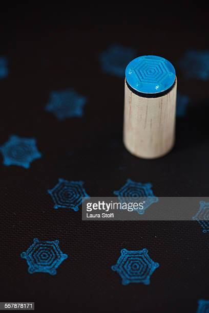 Wooden stamp with snowflake and pale blue ink