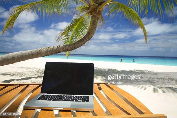 Chaise en bois au coucher du soleil avec ordinateur portable sur la plage de sable, à proximité