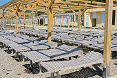 Wooden sun loungers on a pebbled public beach by the sea. Side view.
