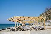 Wooden sun loungers on a pebbled public beach by the sea