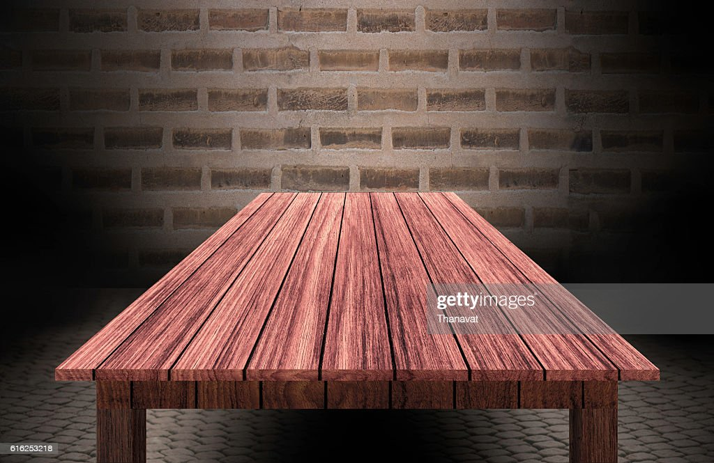 wooden table in front of brick wall : Stock Photo