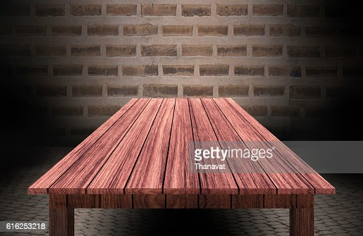 wooden table in front of brick wall : Foto de stock
