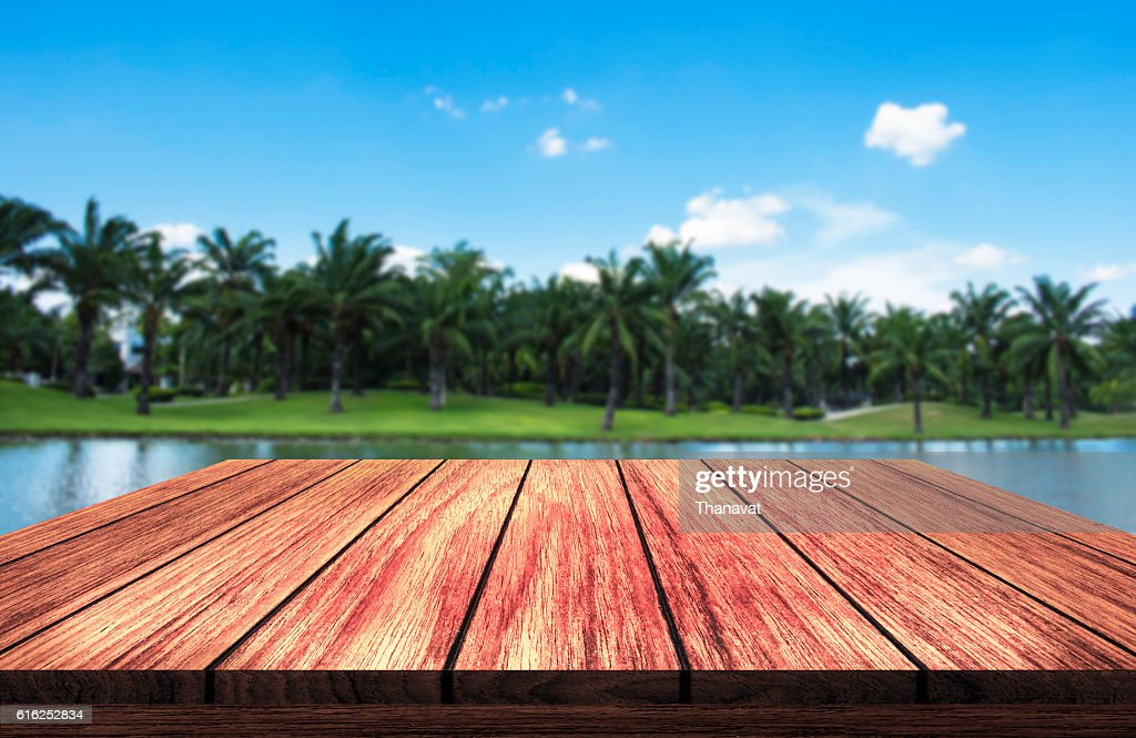 wooden table in front of park and lake background : Foto de stock