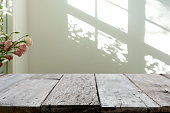 wooden table in front of the blur background with the shadow of tree flower and window