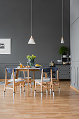 Wooden table in grey dining room interior design
