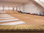 3D render of a wooden table looking out to a defocussed gym interior
