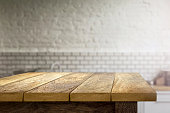 Wooden table on blurred background of kitchen. Focus on foreground
