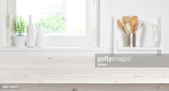 Wooden table on blurred background of kitchen window and shelves : Foto stock