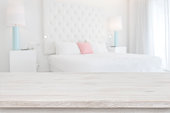 Wooden table top in front of blurred bedroom interior background