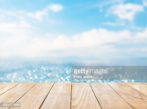 Wooden table top on blue sea and white sand beach : Stock Photo