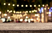 wooden table with abstract bokeh in night shopping mall  background