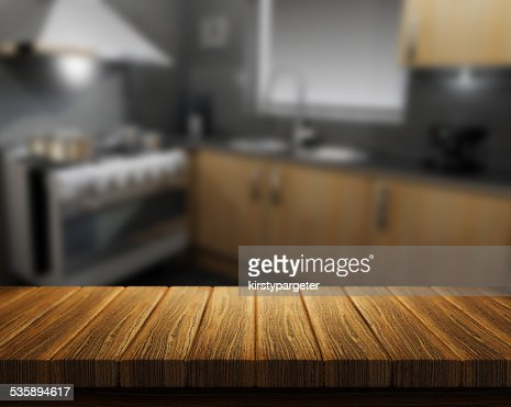 Wooden table with kitchen in background : Stock Photo